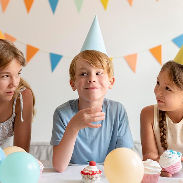 Drei glückliche Kinder mit Geburtstagshüten und Luftballons sitzen am Tisch und essen Muffins