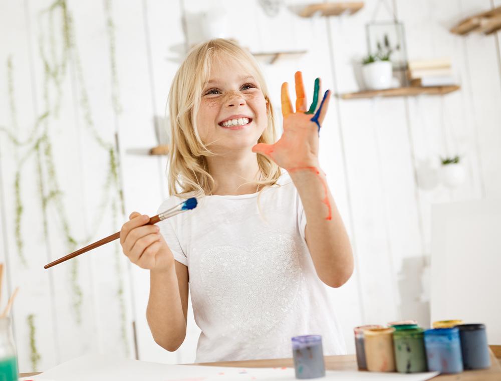 Grinsendes junges Mädchen steht hinter einem Tisch mit Papier und Acrylfarben, hält einen Pinsel in der rechten Hand und präsentiert ihre bemalte linke Hand