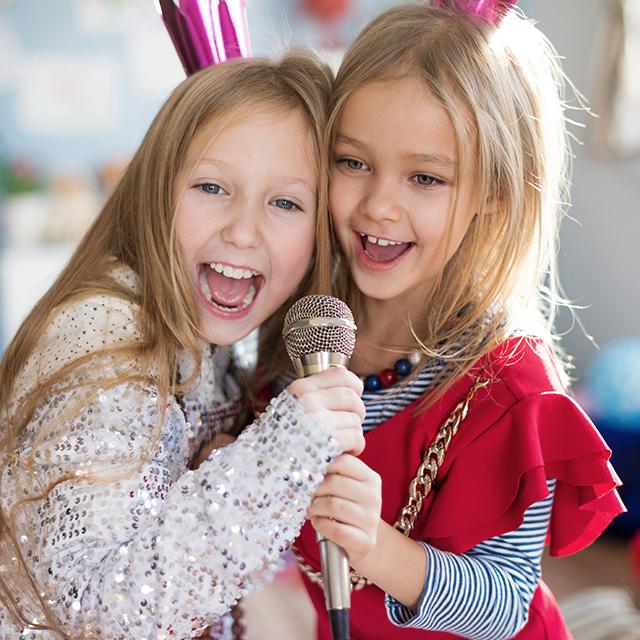 Zwei fröhliche verkleidete junge Mädchen singen in ein Mikrofon
