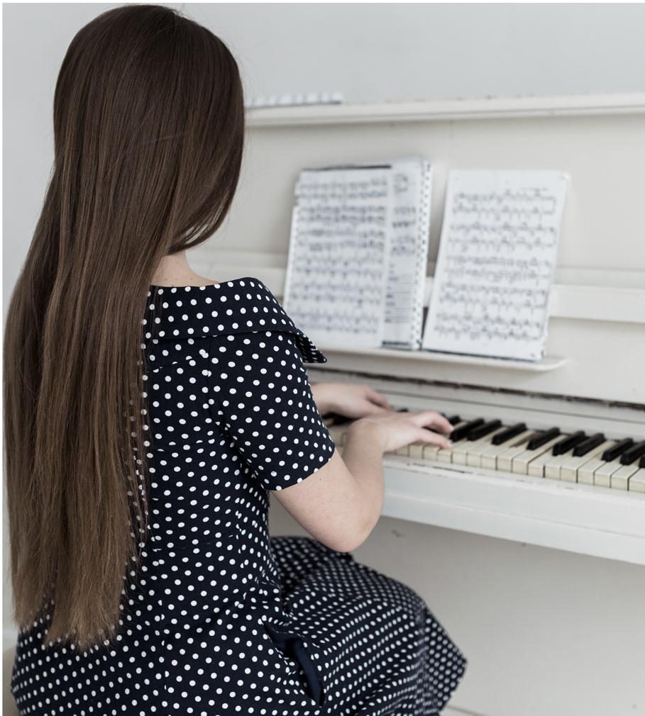 Junge Frau von hinten, sitzt und spielt am Klavier