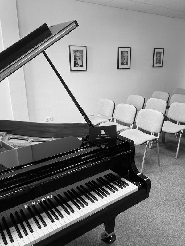 Konzertsaal der Klavierschule Ulm mit Piano im Vordergrund und Stühlen dahinter
