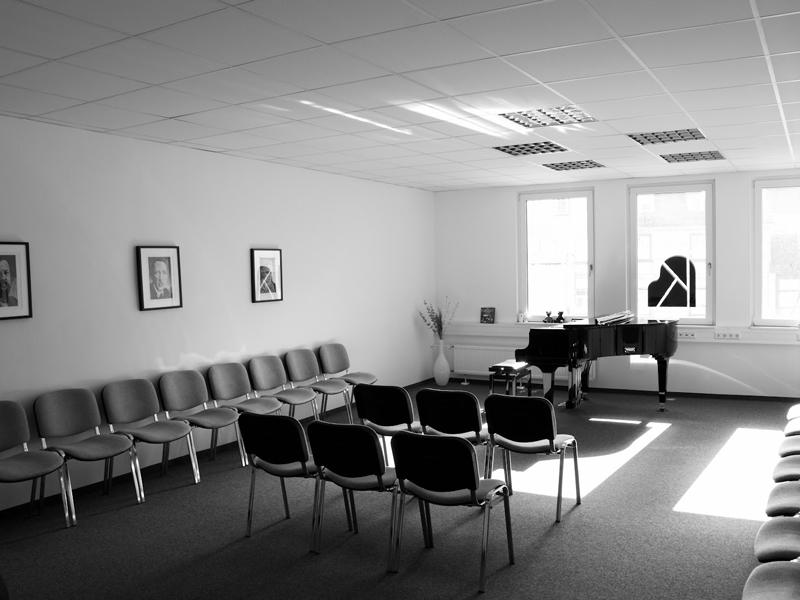 Kleiner, heller Konzertsaal der Klavierschule Ulm mit Piano und Stühlen