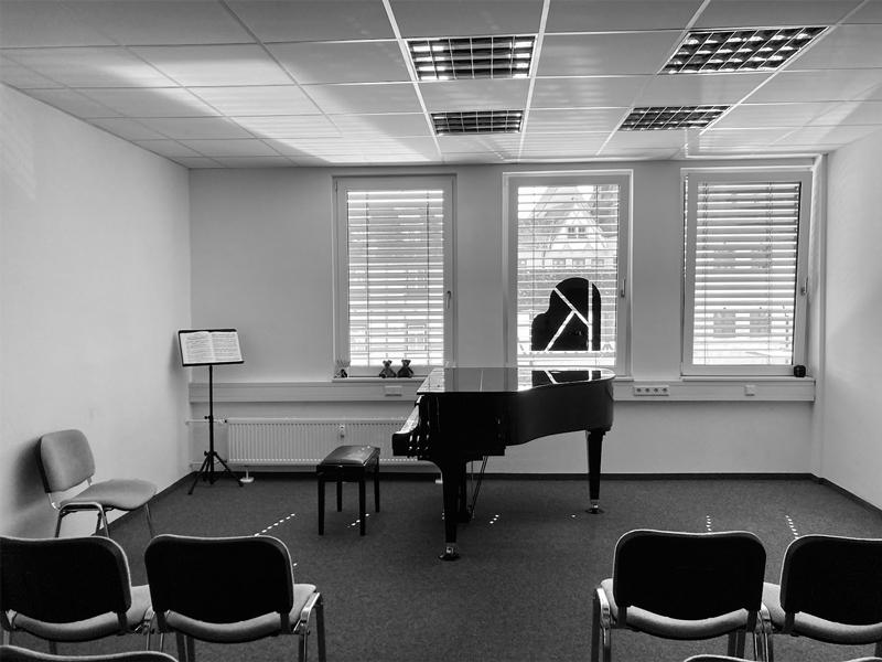 Kleiner Konzertsaal der Klavierschule Ulm mit Piano, Notenständer und Stühlen